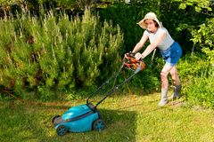 Woman in hat with electric lawn mower on garden background Royalty Free Stock Photos