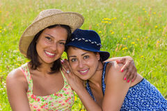 Woman with hat embracing  friend in meadow Royalty Free Stock Photos