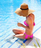 Woman in a hat enjoying cocktail in a swimming pool Stock Photos
