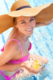 Woman in a hat enjoying cocktail in a swimming pool Royalty Free Stock Photo