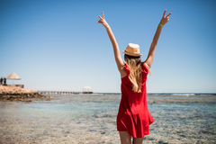 Woman in hat enjoying freedom on a ocean shore with hands raised on sea background. Summer vocation. Royalty Free Stock Photography