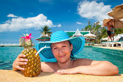 Woman in hat enjoying pineapple drink on holidays Stock Images