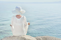 Woman with a hat facing the sea meditating. High key image of a woman with a hat sitting on the rock facing the sea and meditating Stock Images