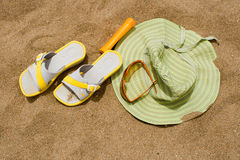 Woman hat, flip flops, sun glasses, sun block on s Royalty Free Stock Photos