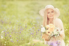 Woman in Hat with Flowers Bouquet, Fashion Model Summer Field Royalty Free Stock Photography