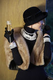 Woman in hat, fur and champagne. Beautiful woman in her mid 40s with blond short hair in a fur stole wearing fresh water pearls and holding a glass of champagne Royalty Free Stock Images