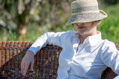 Woman  in hat in the garden. Woman in hat  on her face sitting  in the garden Stock Image