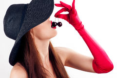 Woman in hat and gloves eating cherries Royalty Free Stock Image