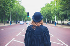 Woman in hat and graduation gown in the street Stock Photos