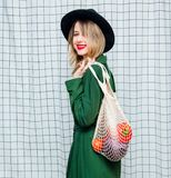 Woman in hat and green cloak in 90s style with net bag. Young style woman in hat and green cloak in 90s style with net bag stay on checkered background royalty free stock images