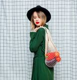 Woman in hat and green cloak in 90s style with net bag. Young style woman in hat and green cloak in 90s style with net bag stay on checkered background stock photo