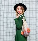Woman in hat and green cloak in 90s style with net bag. Young style woman in hat and green cloak in 90s style with net bag stay on checkered background royalty free stock photography