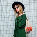 Woman in hat and green cloak in 90s style with net bag. Young style woman in hat and green cloak in 90s style with net bag stay on checkered background royalty free stock photo
