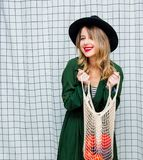 Woman in hat and green cloak in 90s style with net bag. Young style woman in hat and green cloak in 90s style with net bag stay on checkered background stock images