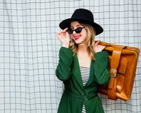 Woman in hat and green cloak in 90s style with travel suitcase. Young style woman in hat and green cloak in 90s style with travel suitcase stay on checkered royalty free stock photos