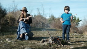 A woman in a hat with a guitar sits by the fire next to the child. stock video