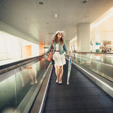 Woman in hat with handbag standing on escalator line at airport Royalty Free Stock Photo