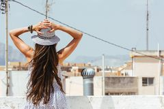 Woman with hat and hands on her head, enjoy the views of the cit Royalty Free Stock Image