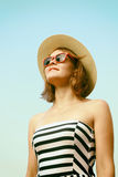 Woman with hat. Happy young woman with hat and sunglasses posing over blue sky Royalty Free Stock Photography