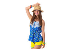 Woman in hat holding hand on her head. Young pretty woman in blue T-shirt and yellow shorts with colored bracelets and hat smiling and holding hand on her head Royalty Free Stock Photo