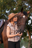 Woman in hat kissing the horse. Royalty Free Stock Photo