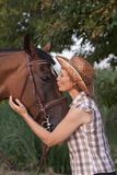 Woman in hat kissing the horse. Royalty Free Stock Photos