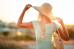 Woman in hat with large fields, at sunset. A slender woman,with long blonde hair in a straw hat with large brim,blue shorts and blue t-shirt,on the shoulder stock photo