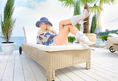 Woman in hat lie on a lounger. Royalty Free Stock Images