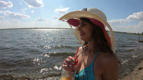 Girl with a glass of juice on the beach. A woman in hat lies on the beach and drinks pineapple juice stock video footage