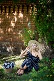 Woman in a hat. In long polka dot dress. Retro italian style royalty free stock image