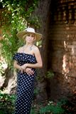Woman in a hat. In long polka dot dress. Retro italian style stock images