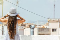 Woman with hat looking at the city on the skyline, from behind, Royalty Free Stock Photography
