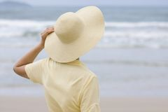 Woman with hat looking at the sea stock photos