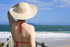 Woman with hat looking at the sea stock images