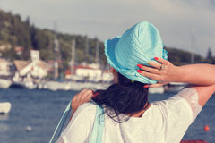 Woman with a hat looking at the sea during sunset Royalty Free Stock Photos