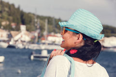 Woman with a hat looking at the sea during sunset Royalty Free Stock Image