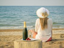 Woman in hat looking at the sunset the sea next to the table with sparkling wine. A full bottle of shaman`s, strawberries and the woman on the beach. The royalty free stock photography