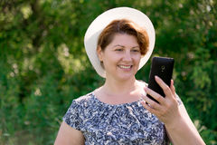 Woman in hat looks at cell phone outside Royalty Free Stock Image