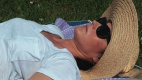 Woman in hat lying on grass stock footage
