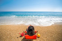 Woman in hat lying on the sunbed. Woman in big hat lying on the red sunbed. Summer vacation concept. Back view with no face Royalty Free Stock Photos