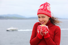 Woman in hat and mittens holds cup of hot tea Stock Photo