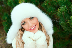 Woman in a hat, mittens, scarves, sweaters, fur in winter fir forest Royalty Free Stock Image