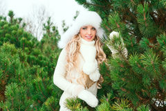 Woman in a hat, mittens, scarves, sweaters, fur in winter fir forest Royalty Free Stock Images