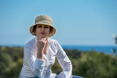 Woman  in hat in nature. Woman in hat sitting  in nature with blue sky background Royalty Free Stock Image