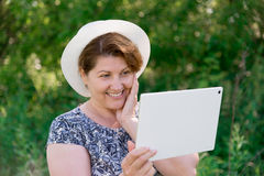 Woman in hat with pc tablet outside Stock Images