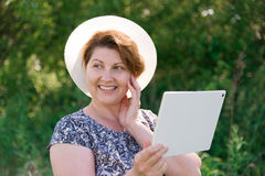 Woman in hat with pc tablet outside Stock Photos