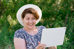 Woman in hat with pc tablet outside Stock Image