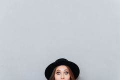 Woman in hat peeping out from the edge Royalty Free Stock Image