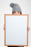 Woman in hat peeping over blank board Royalty Free Stock Photography