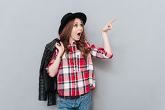 Woman in hat and plaid shirt pointing finger away Stock Image